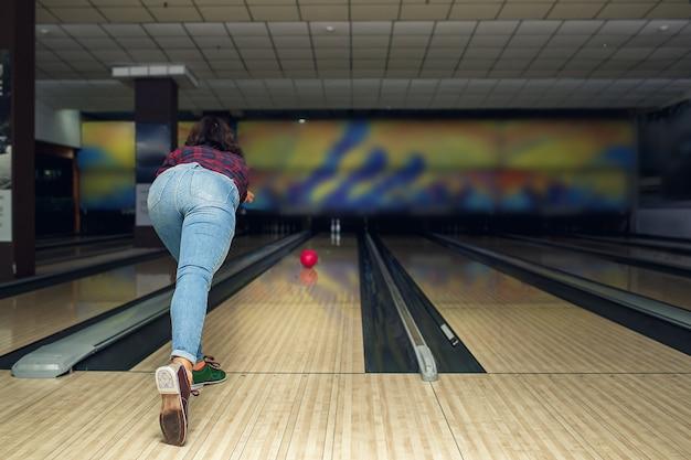 Bella ragazza gioca a bowling nel club di bowling