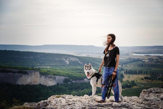 Bella ragazza gioca con un cane, husky grigio e bianco, in montagna al tramonto. ragazza indiana e il suo lupo