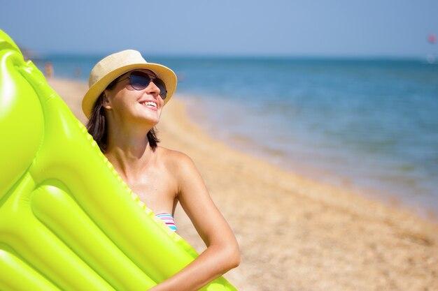 Bellissimo ritratto di ragazza con materasso galleggiante gonfiabile su sfondo estivo spiaggia con spazio copia
