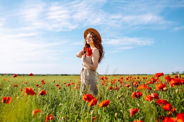 Bella ragazza in posa in un campo di papaveri