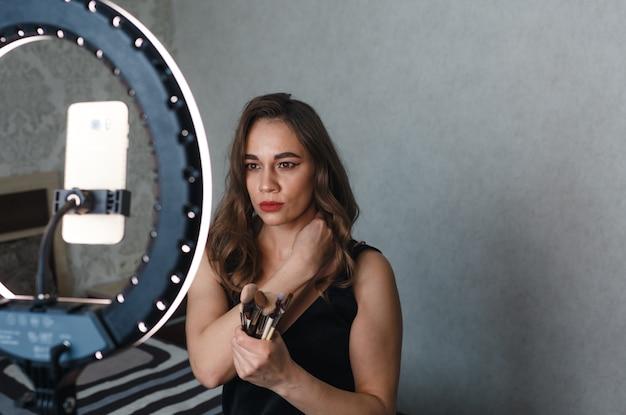 Una bella ragazza si trucca il viso con un pennello e scatta foto di se stessa al telefono