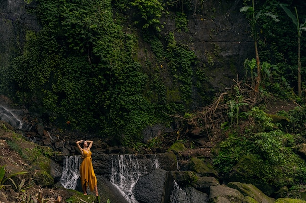 Bella ragazza che alza entrambe le braccia mentre sente la libertà al momento, fiume di montagna veloce che scorre nella giungla jungle