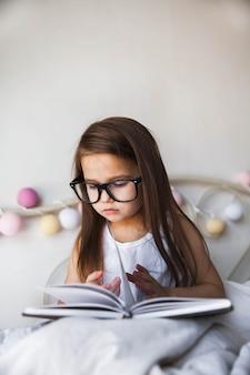 Bella ragazza che legge un libro a letto con gli occhiali, istruzione, interessi, potenziale studente