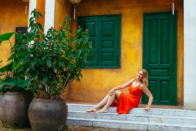 Una bella ragazza in un vestito rosso si siede contro un muro giallo con una porta verde e una finestra con lanterne cinesi. architettura dell'antica città di hoi an. vietnam.