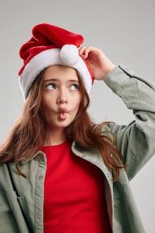Bella ragazza con un cappello rosso con un pompon su uno sfondo grigio e un modello di giacca t-shirt