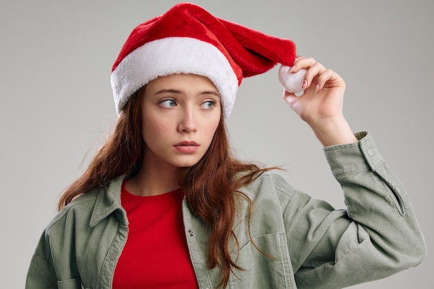 Bella ragazza con un cappello rosso con un morbido pompon su uno sfondo grigio e vista ritagliata