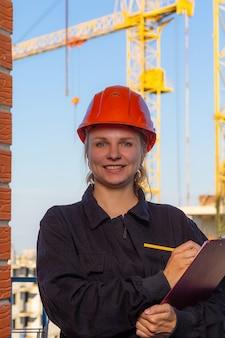 Bella ragazza con un casco rosso e un'uniforme con un sorriso sul viso