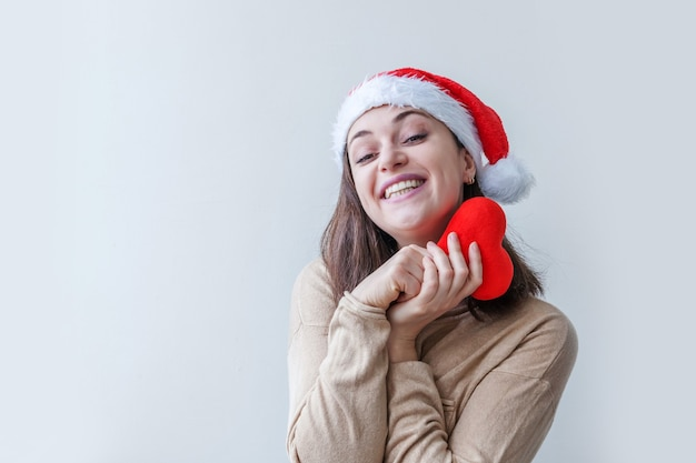 Bella ragazza in cappello rosso di babbo natale che tiene in mano il cuore rosso isolato su sfondo bianco. ritratto di giovane donna, emozioni vere. buon natale e concetto di vacanze di capodanno.