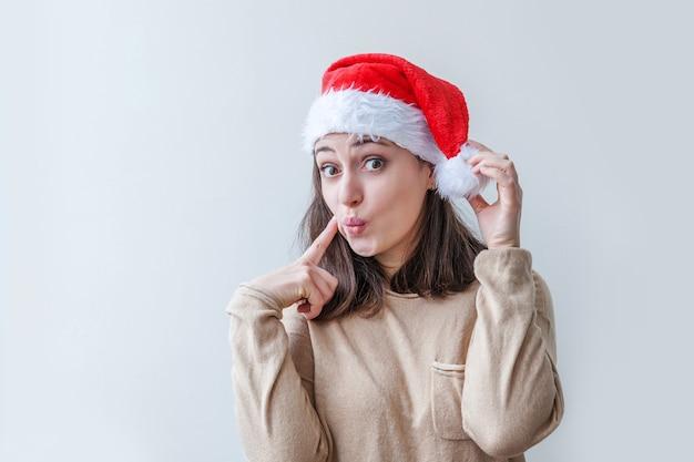 Bella ragazza in cappello rosso di babbo natale isolato su sfondo bianco