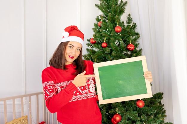 Una bella ragazza con un maglione rosso nella stanza dei bambini vicino all'albero di natale