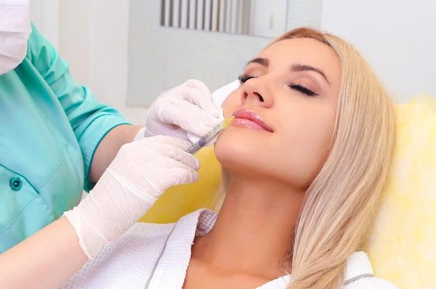 Bella ragazza sulla procedura di ringiovanimento nell'iniezione di riempimento della clinica di bellezza