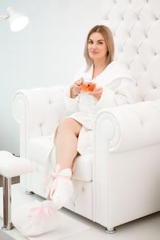 La bella ragazza si rilassa in un accappatoio bianco con una tazza di tè nelle sue mani nello spasalone.