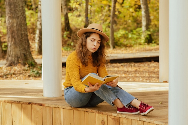 Bella ragazza che si rilassa nel parco in autunno con un libro