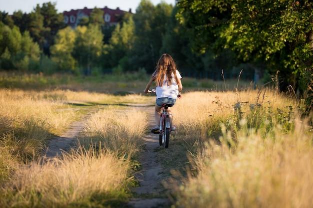 Bella ragazza in sella a una bici nei campi al tramonto