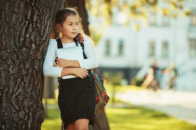 Una bella ragazza in età scolare è in piedi da un albero e tiene in mano un tablet. studentessa vestita di prendisole