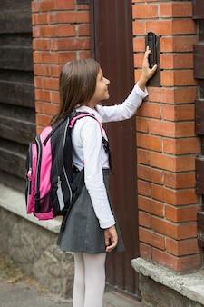 Bella ragazza in uniforme scolastica premendo il pulsante del citofono