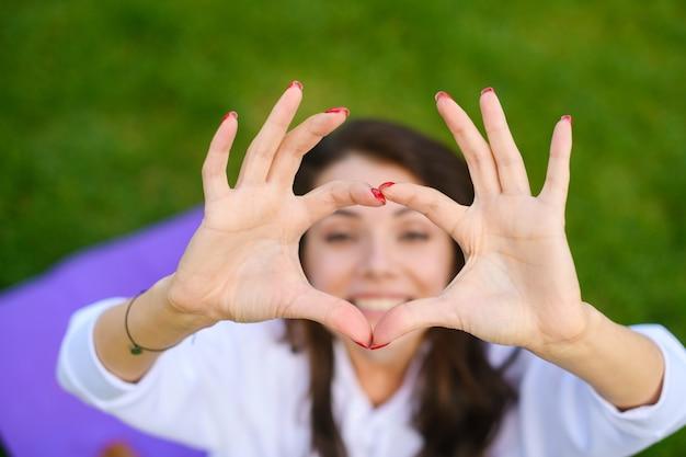 La bella ragazza si siede sul tappetino al parco verde, alza le mani in posizione yoga mudra e guarda sorridere con le dita