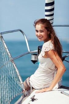 Bella ragazza seduta sulla prua di una barca a vela