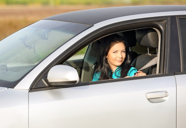 Bella ragazza seduta in macchina e si mette la cintura di sicurezza
