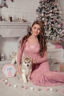 Bella ragazza che si siede vicino all'albero di natale con il cucciolo