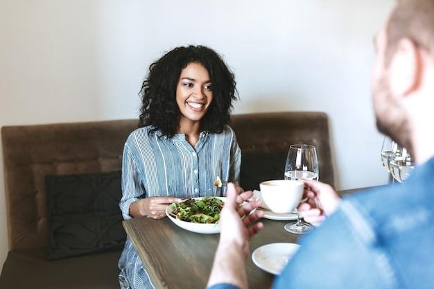 Bella ragazza seduta al ristorante con un amico e mangiare insalata. signora afroamericana sorridente che mangia insalata al caffè