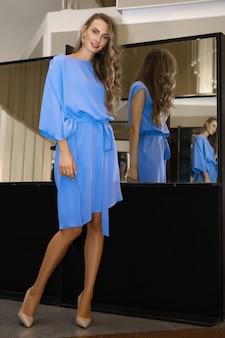 Bella ragazza in abito blu cielo vicino allo specchio con riflessi multipli
