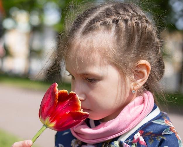 Bella ragazza profumata tulipano rosso contro la primavera fiorita