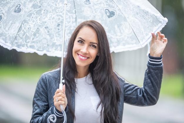 La bella ragazza sorride alla macchina fotografica che tiene un ombrello per proteggerla dalla pioggia.