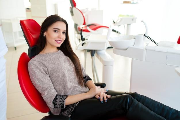 Bella ragazza sorride sulla poltrona del dentista.
