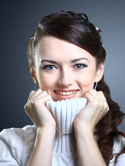 Bella ragazza sorride in un maglione isolato su uno sfondo grigio