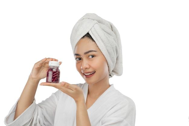Bella ragazza che sorride con un asciugamano con un gesto di due mani che presenta una bottiglia di vitamine