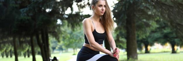 La bella ragazza in abiti sportivi flette i piedi dei muscoli.