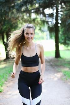 Bella ragazza in abiti sportivi corre nel parco estivo