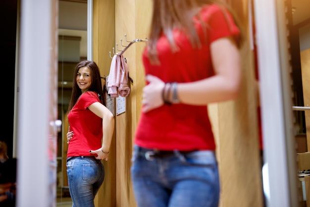 Bella ragazza in piedi davanti a uno specchio è felice di come le appare la sua nuova maglietta.