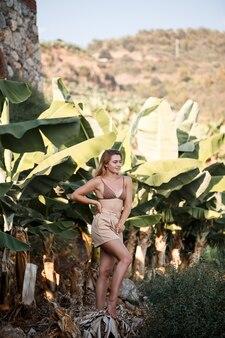 Una bella ragazza si trova in una bella posa vicino a una palma, ritratto in una piantagione di banane