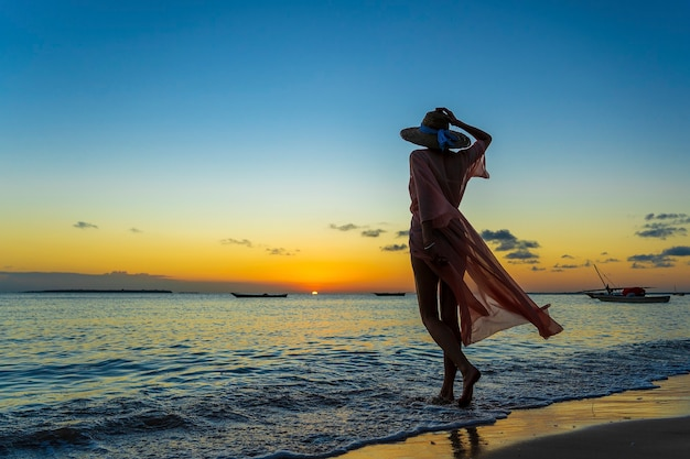Bella ragazza in un cappello di paglia e pareo sulla spiaggia durante il tramonto dell'isola di zanzibar, tanzania, africa orientale. concetto di viaggio e vacanza