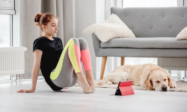 Bella ragazza allunga le dita dei piedi durante la lezione di balletto online con il tablet a casa e il cane golden retriever che dorme vicino a lei