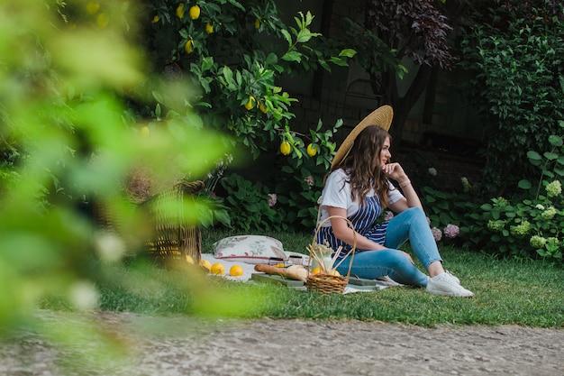 Una bella ragazza con un grembiule a righe e un cappello di paglia si siede su un copriletto