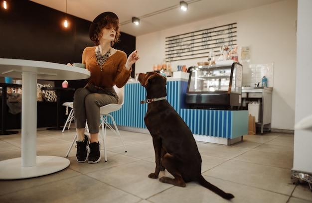 Bella ragazza in vestiti alla moda e cappello che gioca con un cane in un caffè amico degli animali