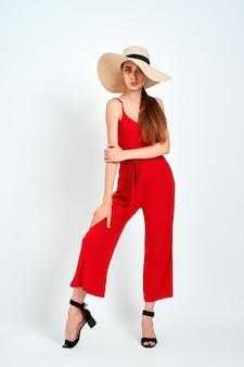 Bella ragazza in cappello da sole in piedi su sfondo bianco in studio in elegante tuta rossa