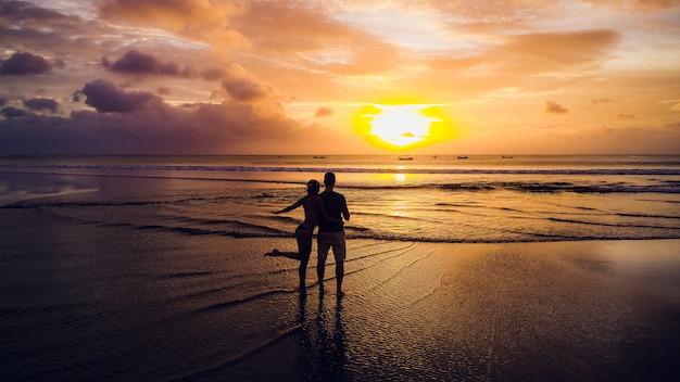 Bella ragazza su sfondo tramonto sulla spiaggia di sabbia