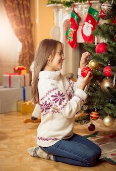 Bella ragazza in maglione seduta sul pavimento in soggiorno e decorare l'albero di natale