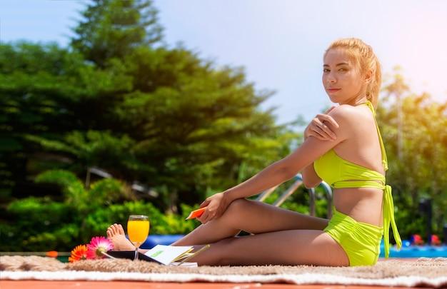 La bella ragazza in costume da bagno sta indossando felicemente un sunblock alla piscina sulla sua festa.