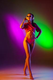 Bella ragazza in costume da bagno sul fondo dello studio al neon