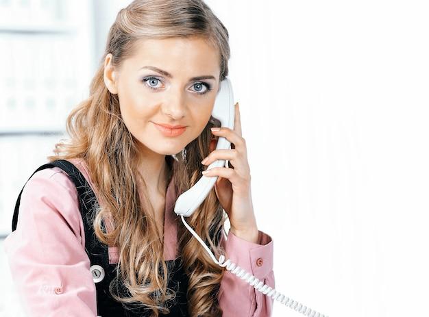 Bella ragazza che parla al telefono e sorride alla macchina fotografica.