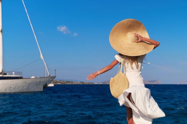 Turista della bella ragazza che cammina al porto marittimo del porticciolo di spetses, grecia.
