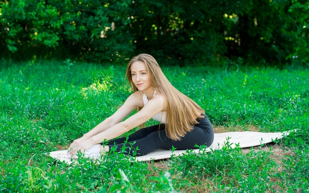 Bella ragazza si allena nella natura e medita