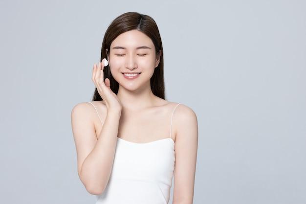 Bella ragazza che utilizza un prodotto di bellezza