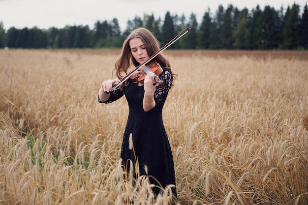 Bella ragazza violinista gode di suonare il violino sulla maturazione del campo di grano