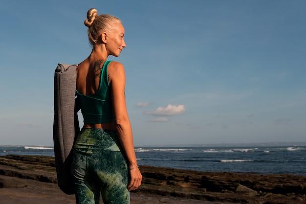 Bella ragazza che cammina sulla spiaggia con il tappetino da yoga